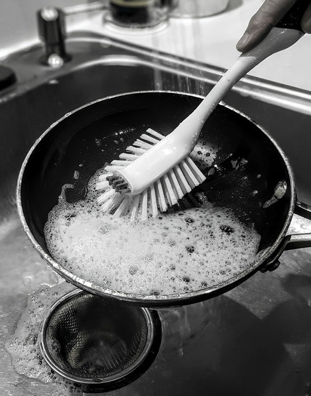 cleaning carbon steel pan with brushes